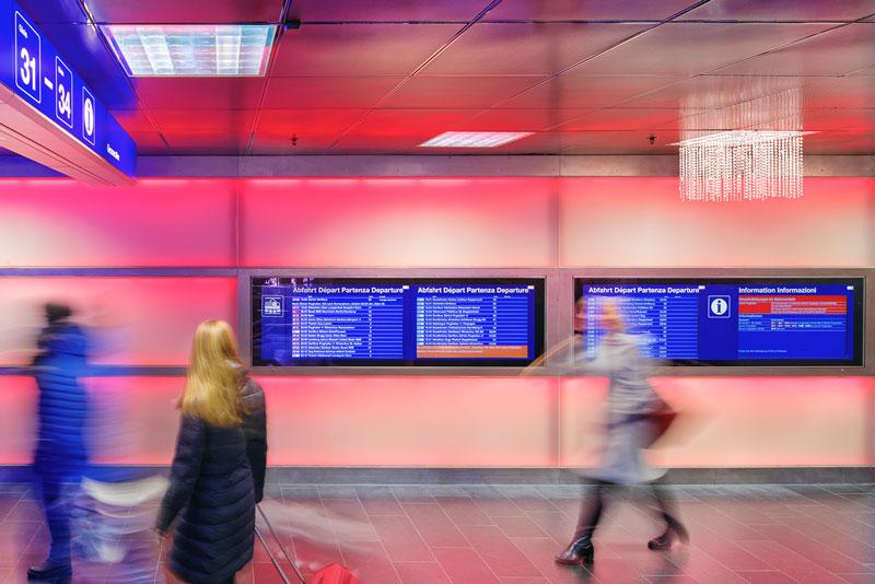 Eine Frau im langen Daunenmantel beobachtet die Fahrgastinformationsmonitore, die in die rot hinterleuchteten Wände des Züricher Hauptbahnhofes eingelassen sind.